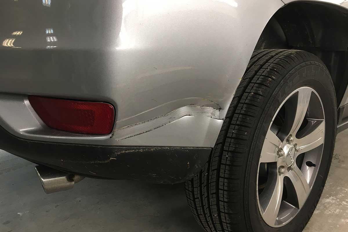gray SUV larger scratch and dent before